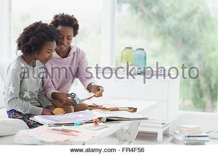 mother helping preteen daughter with scrapbook - Stock Photo