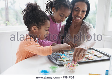 mother and young daughters making cookies - Stock Photo