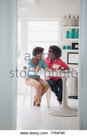 mother and daughter sharing a laugh in the kitchen - Stock Photo