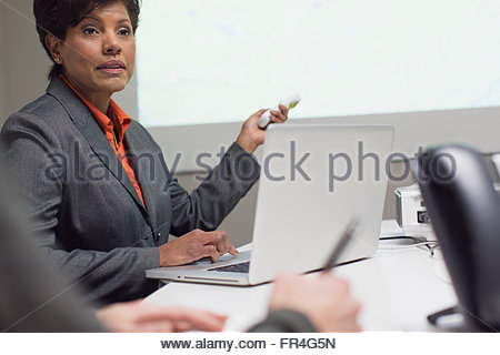 Mature businesswoman using projector at meeting. - Stock Photo
