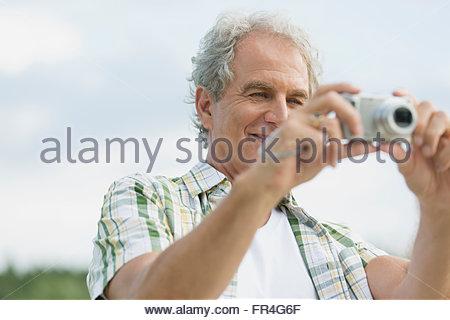 Attractive senior man focusing camera outdoors. - Stock Photo