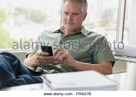 Relaxed businessman texting on cell phone in office. - Stock Photo