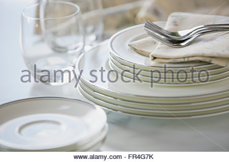 Close-up of gleaming fine china stacked on counter. - Stock Photo
