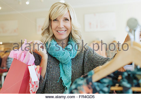 Portrait of pretty, middle-aged woman shopping at clothing store. - Stock Photo