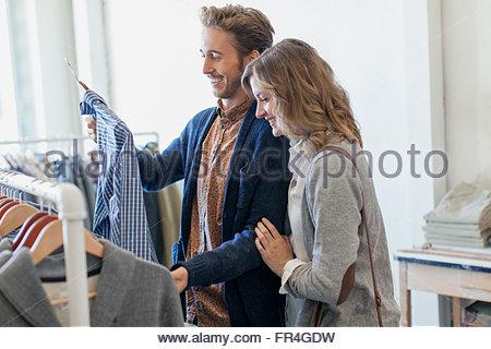 Couple admiring shirt from clothing rack. - Stock Photo