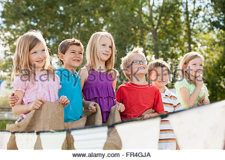Young cousins waiting to start potato sack race. - Stock Photo