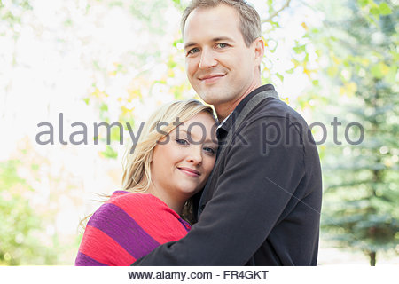 Portrait of attractive husband and wife hugging each other. - Stock Photo