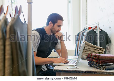 Young adult sales clerk working on laptop in mens wear store. - Stock Photo