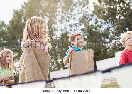 Cousins competing in a potato sack race. - Stock Photo