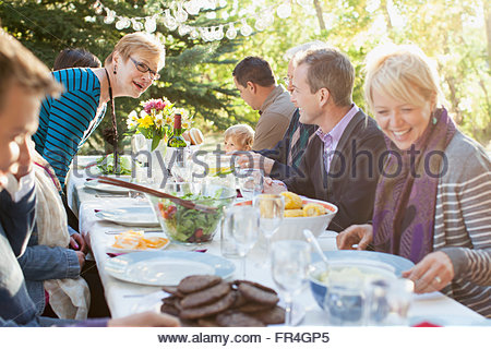 Three generations of family enjoying a meal outdoors. - Stock Photo