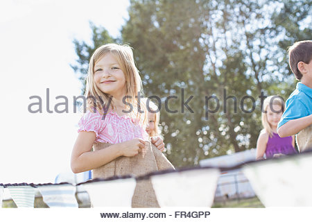 Cute, blond girl racing in potato sack race. - Stock Photo