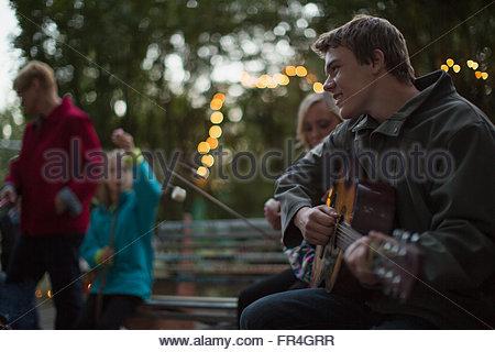 Teenage boy playing guitar outdoors at family reunion. - Stock Photo