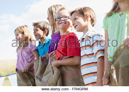 Children lined up to compete in potato sack race. - Stock Photo