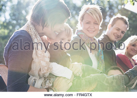 Mom holding two year old son at family reunion. - Stock Photo