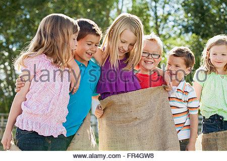 Cousins having fun with potato sacks - Stock Photo