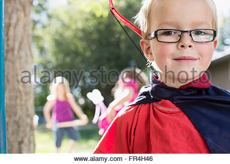 Portrait of six year old boy dressed in cape with bow and - Stock Photo