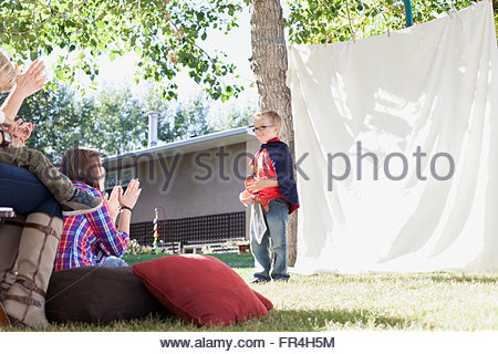Young boy performing a play for family. - Stock Photo