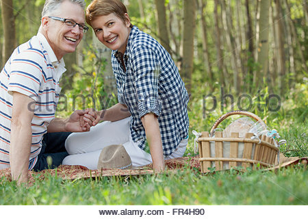 middle-aged couple holding hands while on a picnic - Stock Photo