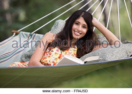 portrait of pretty, mid-adult woman relaxing in hammock - Stock Photo
