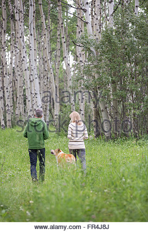 middle-aged couple walking their dog in the woods - Stock Photo