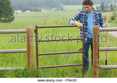middle aged man opening gate to paddock on rural property - Stock Photo