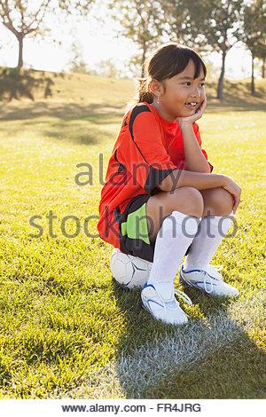 girl soccer player sitting on soccer ball on sidelines - Stock Photo