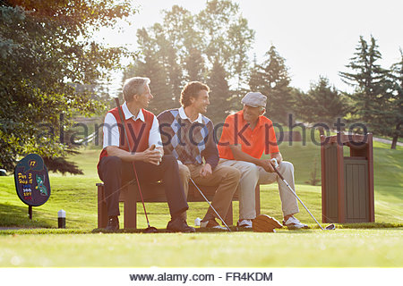 three golfers sitting on bench by tee box - Stock Photo