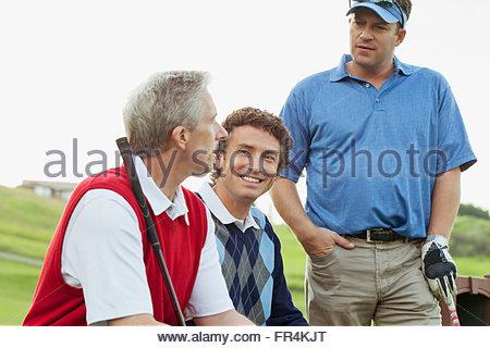golfers sitting on bench having a conversation - Stock Photo