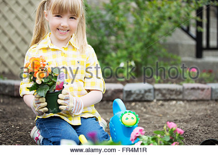 cute, 5 year old girl planting flowers - Stock Photo