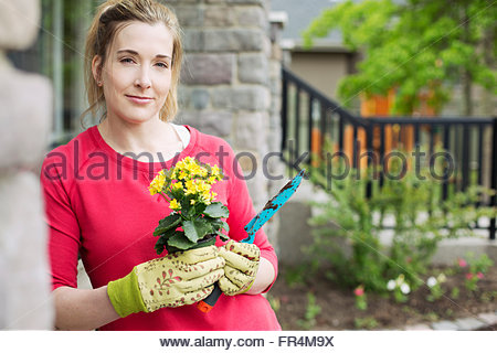 portrait of middle aged woman with flowers - Stock Photo