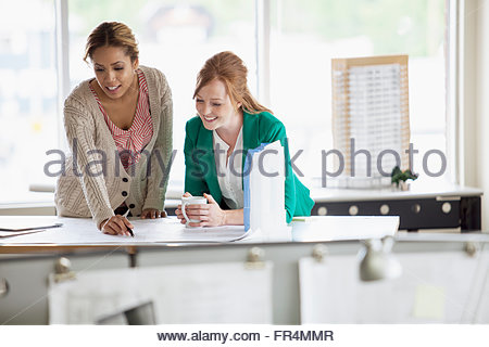 female architects reviewing plans in office - Stock Photo