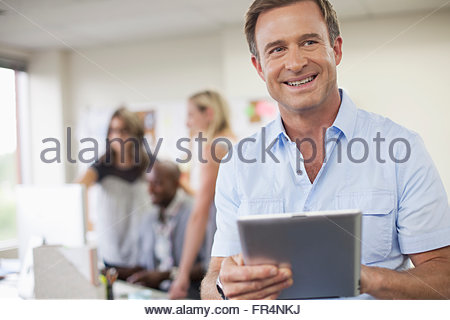 handsome, middle-aged designer in office with pc tablet - Stock Photo