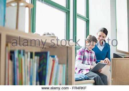 elementary teacher assisting student - Stock Photo