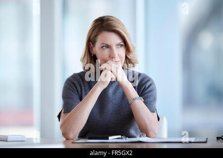 Pensive businesswoman looking away in conference room - Stock Photo