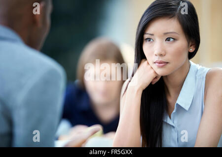 Serious businesswoman listening to businessman - Stock Photo