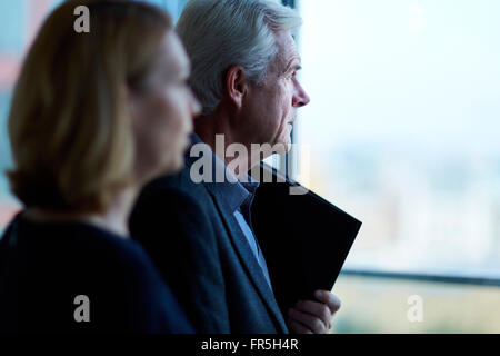 Pensive businessman and businesswoman looking through window - Stock Photo