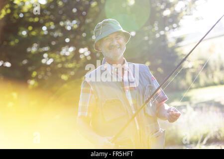 Portrait smiling senior man with fishing rod - Stock Photo