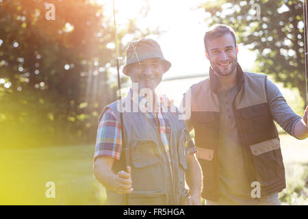 Portrait smiling father and adult son with fishing rods - Stock Photo
