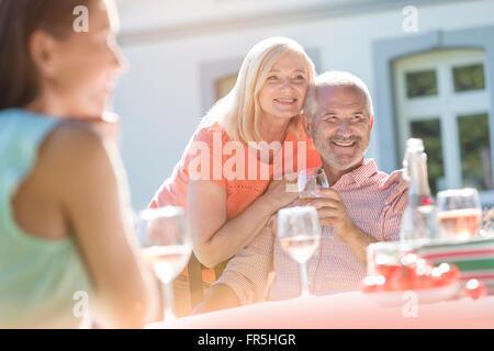 Senior couple smiling and drinking wine on sunny patio - Stock Photo
