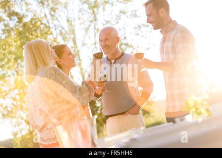 Senior couple and adult children drinking wine on sunny patio - Stock Photo