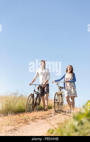 Young couple walking bicycles on dirt road below sunny blue sky - Stock Photo