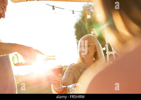 Senior man pouring wine for wife on sunny patio - Stock Photo