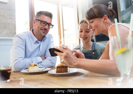 Family with cell phone eating dessert at cafe table - Stock Photo