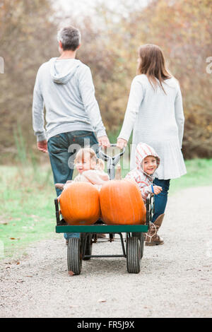 Parents pulling toddler children and pumpkins riding in wagon - Stock Photo