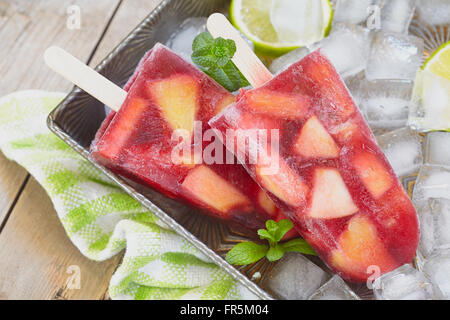 Fresh sangria popsicles with apples, orange and peaches - Stock Photo