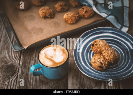 Oatmeal cookies and coffee cup on a wooden table horizontal - Stock Photo