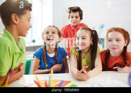 Elementary students talking together at the table - Stock Photo