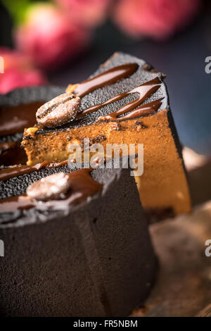 Pieces of coffee mousse and a bouquet of roses on a blue table vertical - Stock Photo