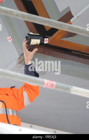 Hamburg, Germany. 21st Mar, 2016. A worker placing a Champagne bottle between the two parts of the bridge at motorway - Stock Photo