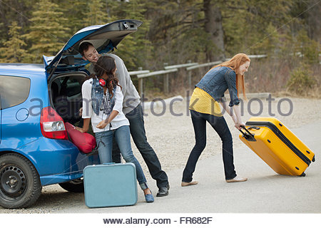 friends unpacking luggage from car - Stock Photo